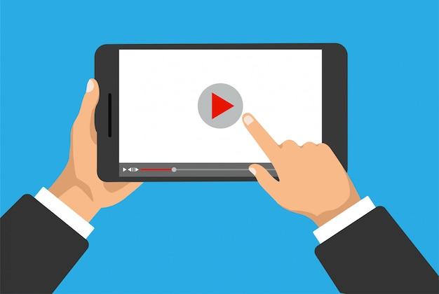 手は、ディスプレイ上の携帯電話またはビデオプレーヤーとデジタルタブレットを保持しています。指でクリックして再生アイコンをクリックします。映画のコンセプト。