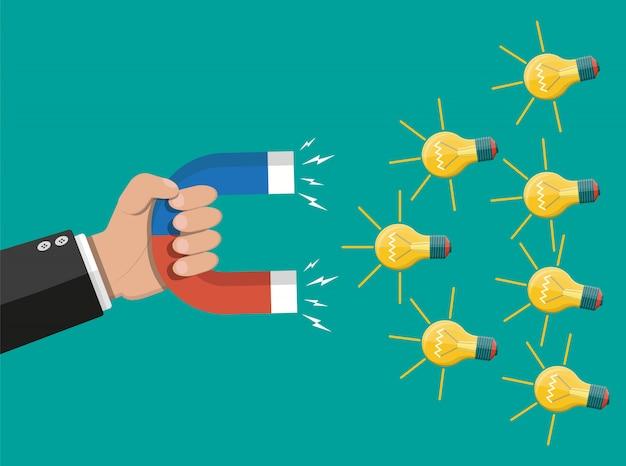 電球のアイデアを引き付ける磁石を持つ手