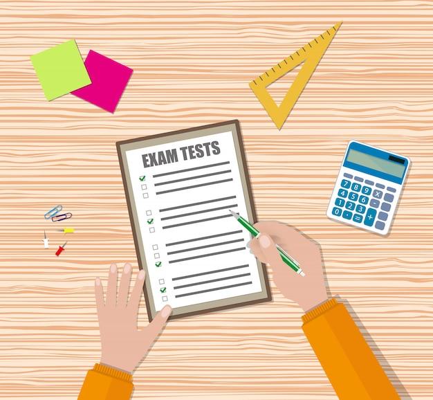 学生の手が試験クイズ用紙に記入します
