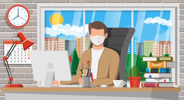 Человек в медицинской маске работает на своем компьютере
