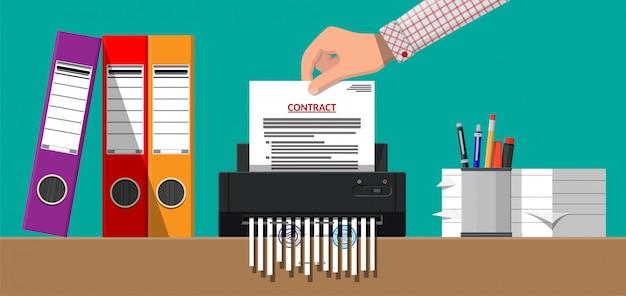 Рука положить контракт бумаги в шредер.
