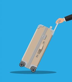 手に旅行バッグ。車輪付きトロリー