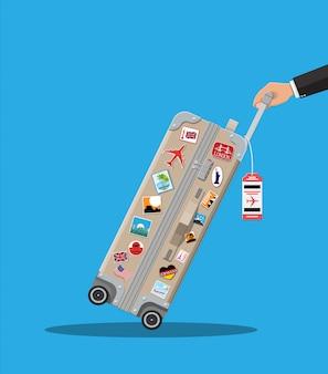 Дорожная сумка в руке. пластиковый кейс с наклейками.