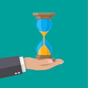 人間の手は古いスタイルの砂時計時計を保持します