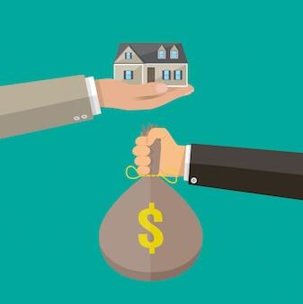 Руки с сумкой денег и дома. недвижимость