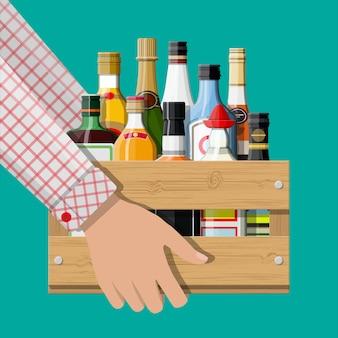 Коллекция алкогольных напитков в коробке в руке