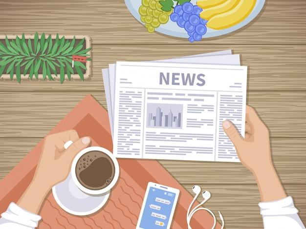 朝食で最新ニュースを読んでいる人。