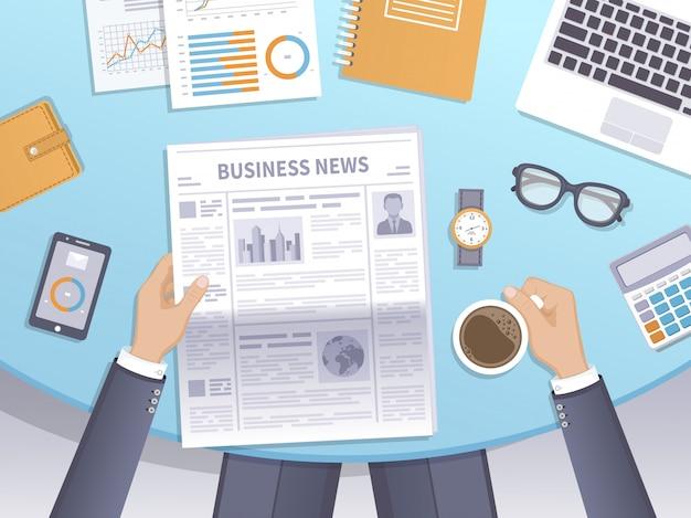 Бизнесмен читает газету на рабочем месте и пьет кофе.