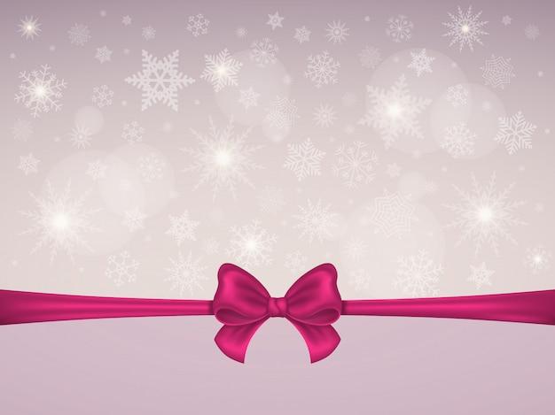 雪片の背景に赤のサテンの弓とリボン。クリスマスのテーマ