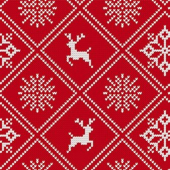 クリスマスは、ムースと雪の結晶の幾何学的な飾りを編んだ。ニットのシームレスな背景。ニット柄