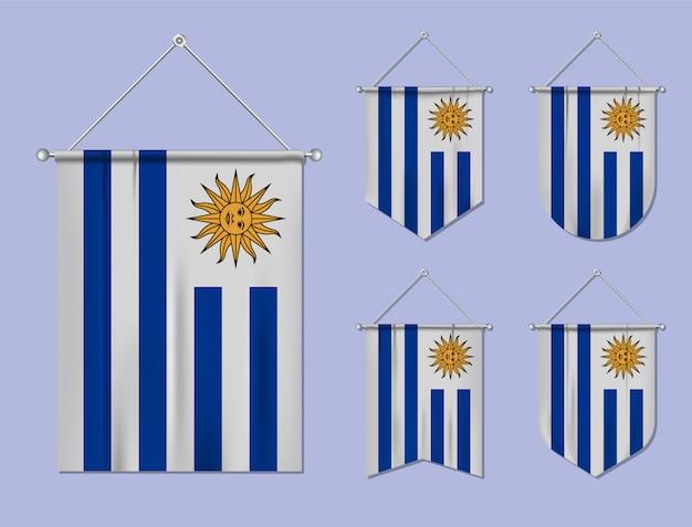 Набор висящих флагов уругвая с текстильной текстурой. разнообразие форм национального флага страны. вертикальный шаблон вымпела.
