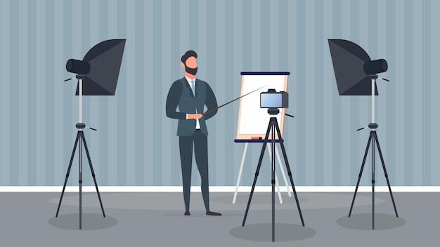ネクタイをしたビジネススーツを着た男性がカメラに向かってプレゼンテーションをしている。先生はレッスンを書いています。ブログ、オンライントレーニング、会議のコンセプト。三脚、ソフトボックスのカメラ。