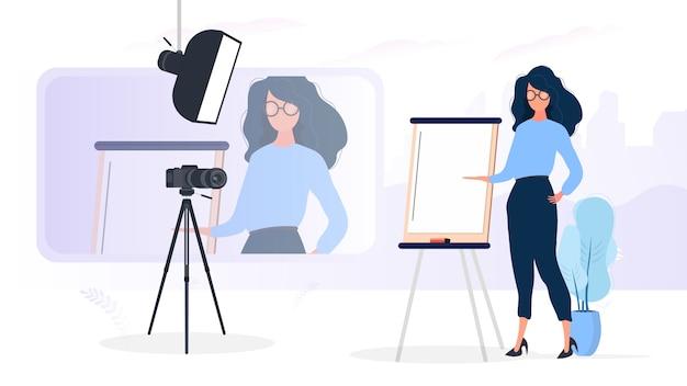 女の子はカメラの前でプレゼンテーションを行っています。先生はオンラインでレッスンを行います。ブログ、オンライントレーニング、会議のコンセプト。三脚、ソフトボックスのカメラ。