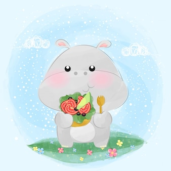 Милый маленький бегемот ест салат