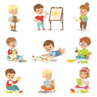 Маленькие дети в художественном классе в школе делают различные творческие занятия, рисование, работа с замазкой и резки бумаги.
