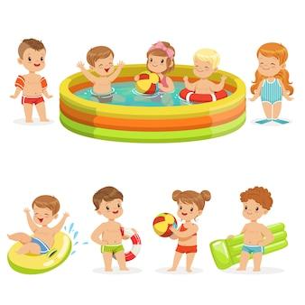 幸せなかわいい漫画のキャラクターのカラフルな水着コレクションでフロートとインフレータブルおもちゃでプールの水で楽しんでいる小さな子供