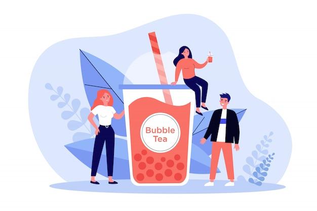 バブルミルクティーのプラスチックカップを持つ人々
