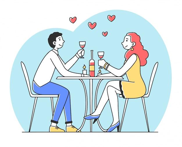 ロマンチックなディナーでレストランに座っている若いカップル