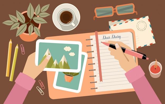 Руки женщины держа ручку и писать в дневнике. персональное планирование и организация. рабочее место