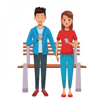 Пара с помощью смартфонов на скамейке