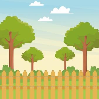 木と木製のフェンスのある公園