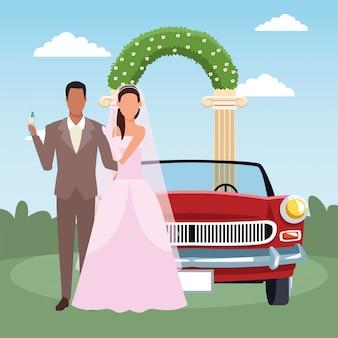 ちょうど結婚されていたカップルに立って、花のアーチと風景の上の古典的な車