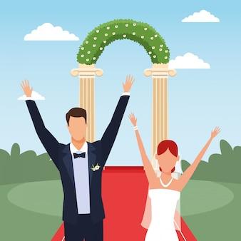 花のアーチと風景の上の幸せな結婚式のカップル