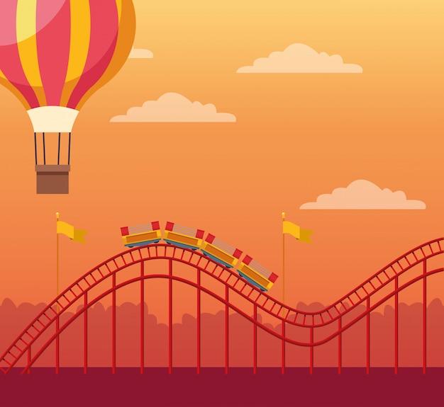 オレンジ色の夕日の上の熱気球とジェットコースター