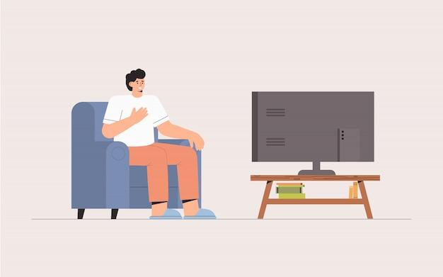 家でテレビのニュースを見てソファに座っている男。衝撃的な内容、否定的なニュース。