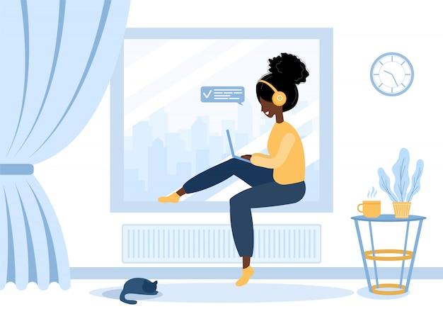 女性のフリーランス。窓辺に座っているラップトップでヘッドフォンでアフリカの女の子。仕事、勉強、教育、自宅での仕事の概念図。フラットスタイルのイラスト。