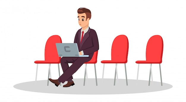 Молодой человек в строгом костюме сидит на стуле с ноутбуком