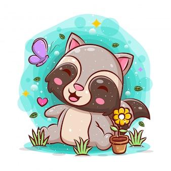 Милый енот сидит в саду