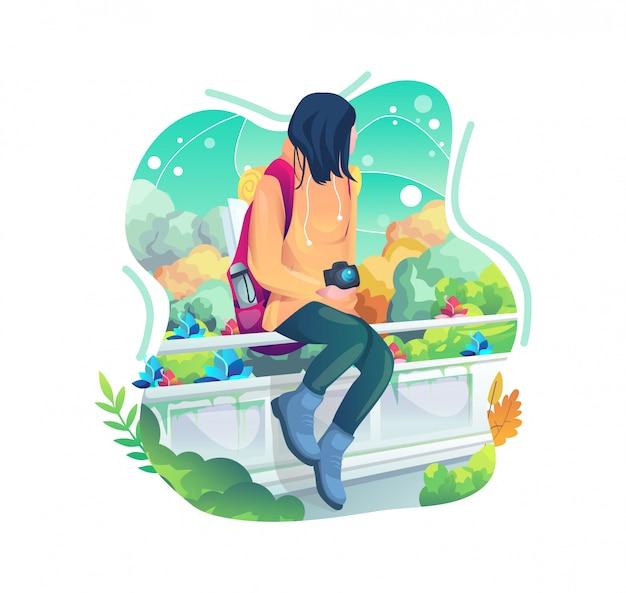 フェンスの上に座っている写真家の女の子