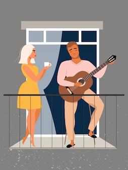 男はバルコニーでギターを弾きます。愛のカップル。隔離と自己分離の概念。パンデミックの最中に家にいる家族。ウィンドウで美しいカップル。バルコニーに立っている男女。