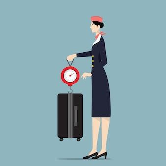 スケールで荷物を重み付けする航空ホステス。