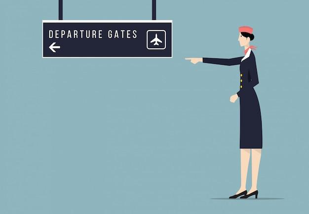 航空会社のホステスは出発ゲートの看板を示しています。
