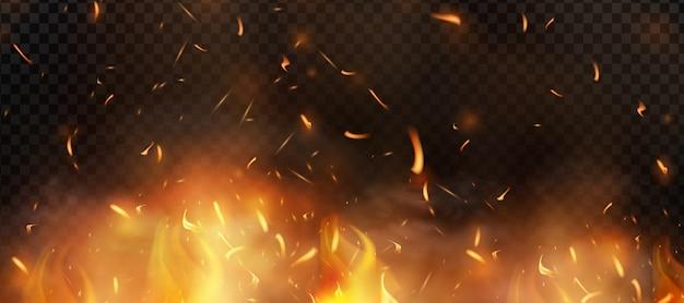 Красный огонь искры взлетают. горящие светящиеся частицы. пламя огня с искрами в воздухе над темной ночью.