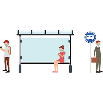 人々はバス停でバスを待ち、社会的距離をとる