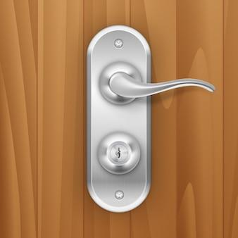 木製の木製の背景に金属製のドアハンドルロック