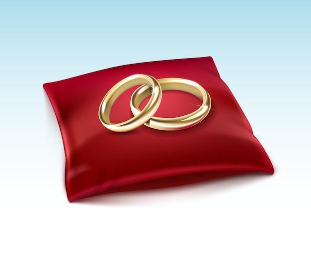 Золотые обручальные кольца на красной атласной подушке, изолированные на белом