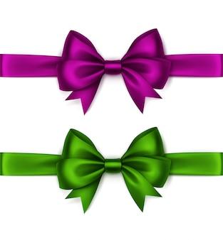 Набор блестящих пурпурный фиолетовый темно-розовый зеленый атласные банты и ленты вид сверху крупным планом на белом фоне