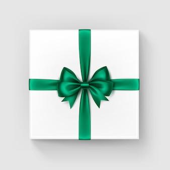 光沢のある明るい緑のエメラルドのサテンの弓とリボンの上面の白い正方形のギフトボックスをクローズアップで孤立した白い背景