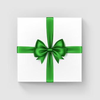 光沢のある明るい緑のサテンの弓とリボンの上面の白い正方形のギフトボックスをクローズアップで孤立した白い背景