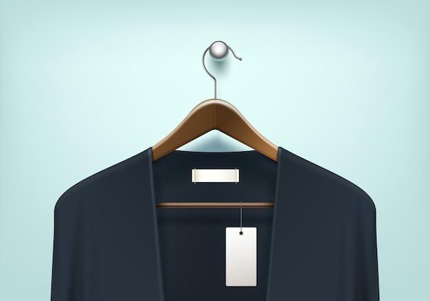 服のコートブラウン木製ハンガーブルーブラックセーターカーディガンジャンパーと空白タグラベルをクローズアップ背景に分離