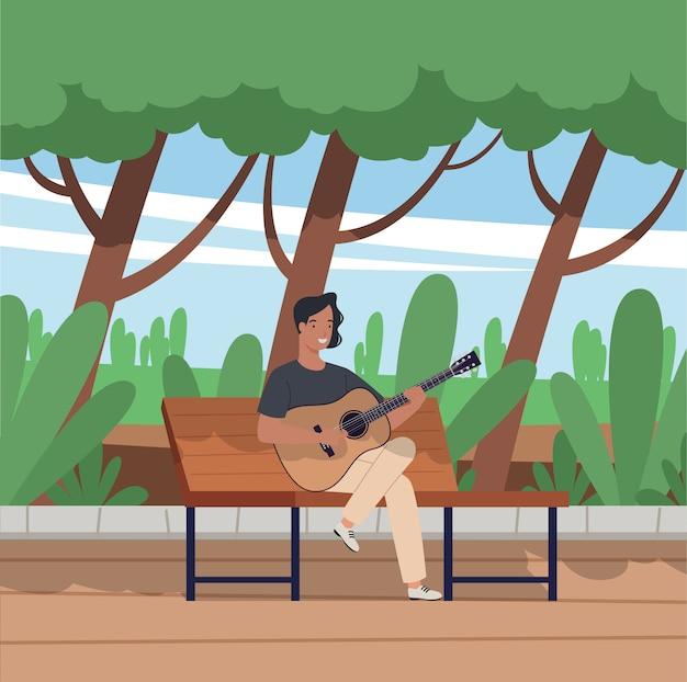 Молодой человек сидит на скамейке и играет на акустической гитаре в парке.