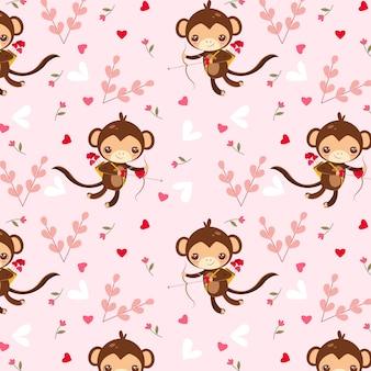 ピンクの背景に猿のキューピッドと心のパターン