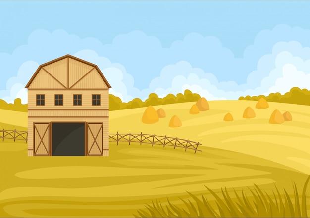 Бежевый сарай с открытыми воротами в поле с стогом сена.
