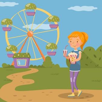 カラフルなイラストの遊園地の観覧車の前でポップコーンとソーダのプラスチック製のカップで立っている笑顔の女の子