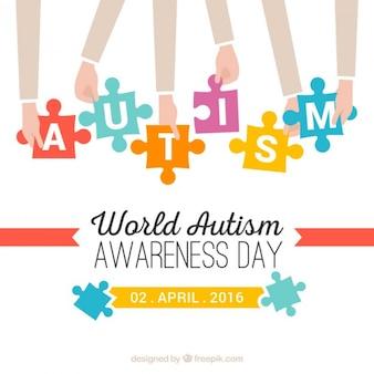 パズルのピース自閉症の日の背景を持つ手