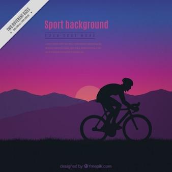 サイクリストのシルエットと日没の背景